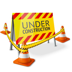 Bright Under Construction sign with orange stripped road cones
