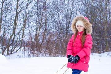 Little girl going sledding in snowy winter day