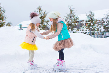Adorable little girls skating on ice rink outdoors in winter