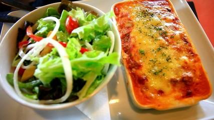 Fresh baked lasagna with vegetable salad. Close up. HD
