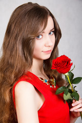 Closeup portrait of a young attractive woman with a red rose