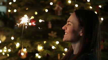 Cheerful young girl with sparkler near decorated Christmas tree