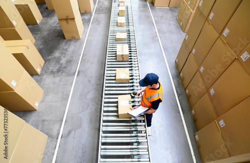 Mann scannt Pakete mit Waren im Versandzentrum ein - 77323536