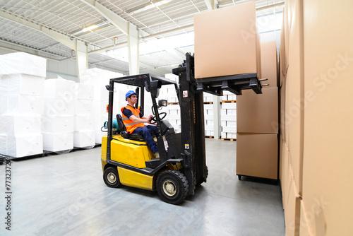 Gabelstaplerfahrer in einem Warenlager // international shipping - 77323727