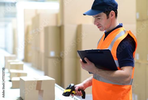 Mann scannt Pakete mit Waren im Versandzentrum ein - 77323730