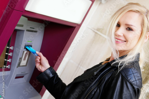 canvas print picture Smiling Woman Inserting a Card in an ATM