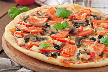 Appetizing pizza with chicken, tomatoes, peppers and mushrooms