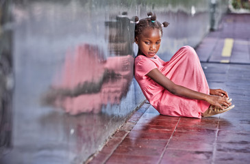 Sad african girl sitting and deeply thinking on the school floor