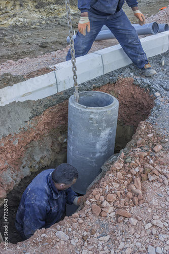 In de dag Tunnel Road worker in trench installing storm drain system