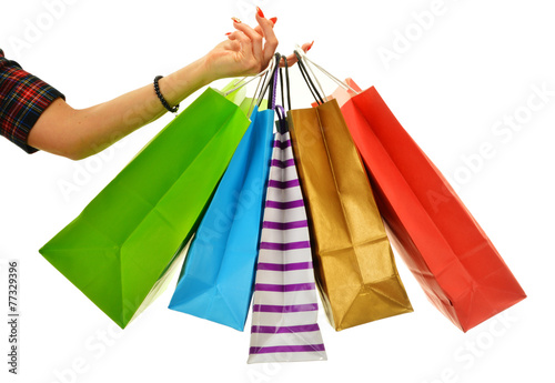 Leinwanddruck Bild Female hand holding paper shopping bags isolated on white