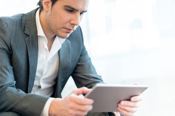 Businessman sitting in his office as he looks at  his tablet com