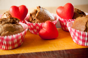 muffins with hearts on wooden desk