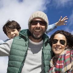 Padres con hijo sonriendo con cielo de fondo