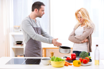 Young attractive couple having an argue while cooking