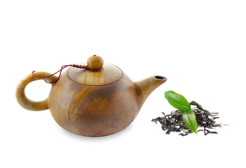stone teapot and green tea leaves on white background