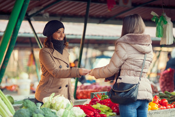 Smiling young woman paying for vegetables at market