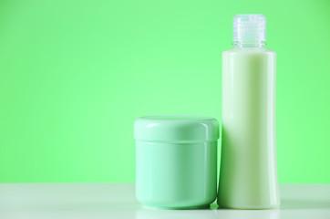 Cosmetic bottles on light green background