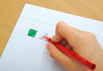 Child drawing red triangle and green square with crayons in