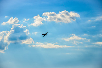 Spitfire in flight on blue cloudy sky over Bratislava