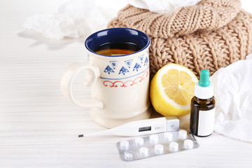 Hot tea for colds, pills and handkerchiefs on table close-up