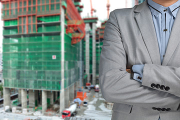 Successful male architect at a building site with arms crossed