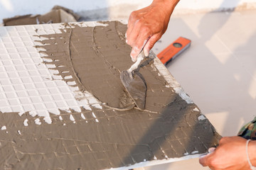 Labor installing tile floor for new house building