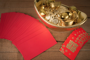 Red pocket and ancient Chinese golden ingots on wooden : with co