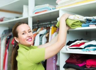 Woman arranging clothes at wardrobe