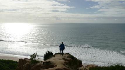 Man Climb on a Cliff Above the Ocean, sunny day