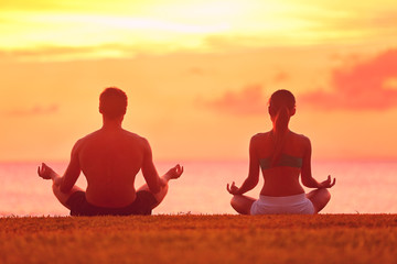 Meditation yoga couple meditating at beach sunset