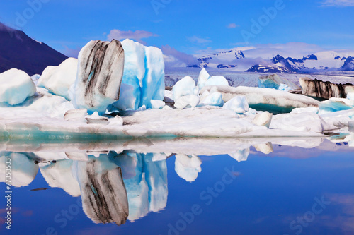 Icebergs  are reflected in water - 77353533