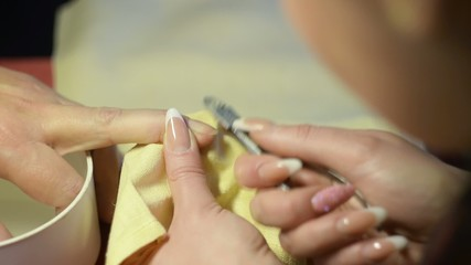 A woman gets her nails trimmed and cleaned