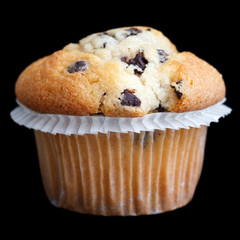 Light chocolate chip muffin in wax liner on black.