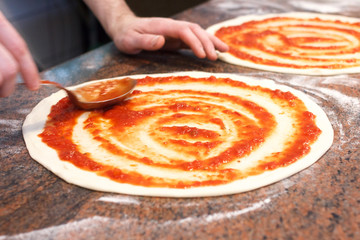 Tomato sauce being spread on pizza base.