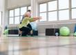 Leinwandbild Motiv Senior woman doing exercise with her personal trainer