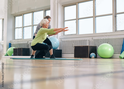 Senior woman doing exercise with her personal trainer - 77361562