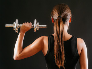 Female doing shoulder press with dumbbell