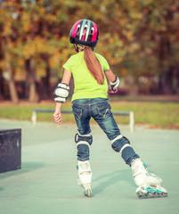 Back view of little girl in helmet on roller-skates in park