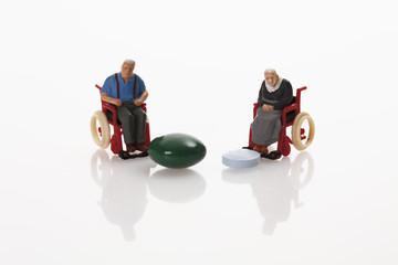 Rentner Figürchen und Pillen auf weißem Hintergrund