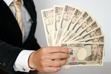お札の束を持つビジネスマン Businessman holding bills