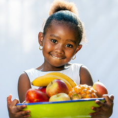Cute african girl holding fruit bowl.