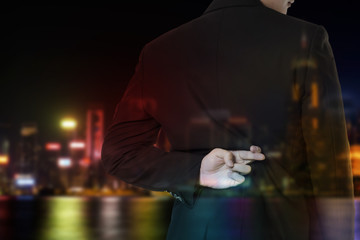 double exposure of businessman cross finger