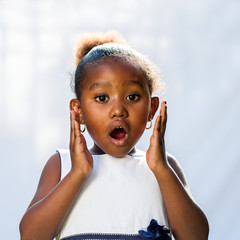 Portrait of cute African girl with shocking face expression.