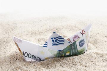 Origami Papierboot von Euro-Banknoten auf Sand