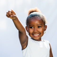 Small African girl pointing with finger into distance.