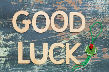 Good luck written with wooden letters and four-leaf clover