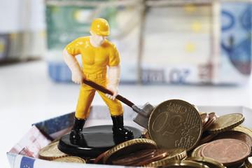 Figurine Arbeiter mit Schaufel, die auf Haufen von Euro-Münzen