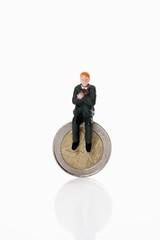 Manager-Figur sitzt auf Euro-Münze