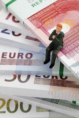 Manager Figur Sitzung vom Stapel von Euro-Banknoten
