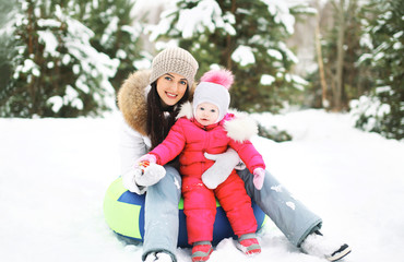 Mother and child on the sled having fun in winter snowy day